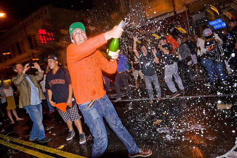 Outdoors, night: man shakes a bottle of champagne over a cheering crowd
