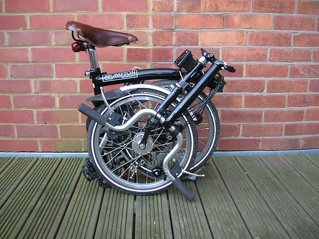 A Brompton bicycle folded, against a brick wall.