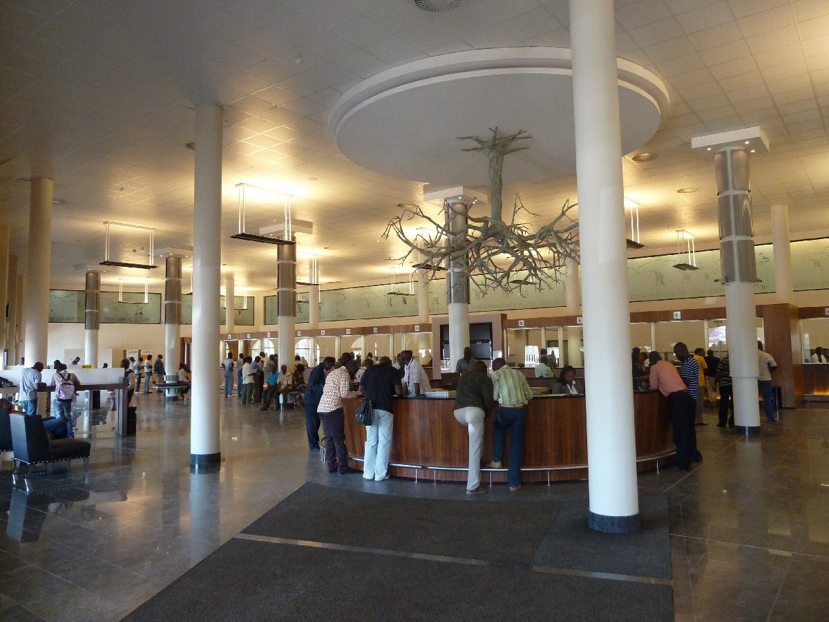 Traditional banking hall with customers, and tellers behind glass